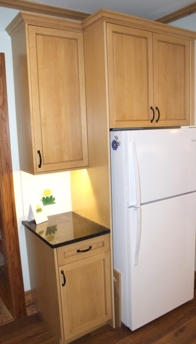 Kitchen cabinets surround refrigerator.