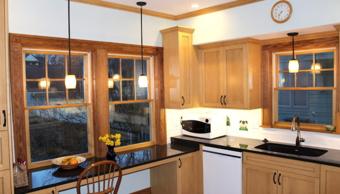 Kitchen counters cabinets and windows.